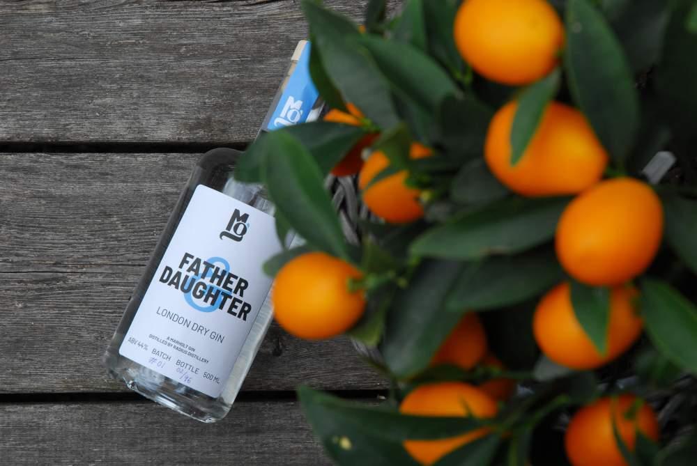 billede af en flaske father & daughter gin i baggrunden med kumquats